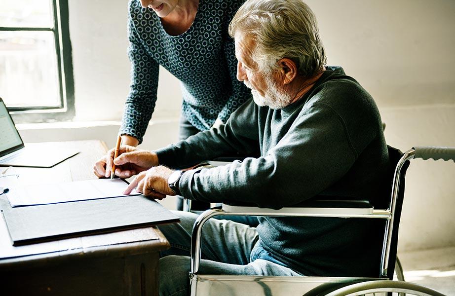 Sterbegeldversicherung - Mann im Rollstuhl unterschreibt mit seiner Frau ein Dokument am Schreibtisch